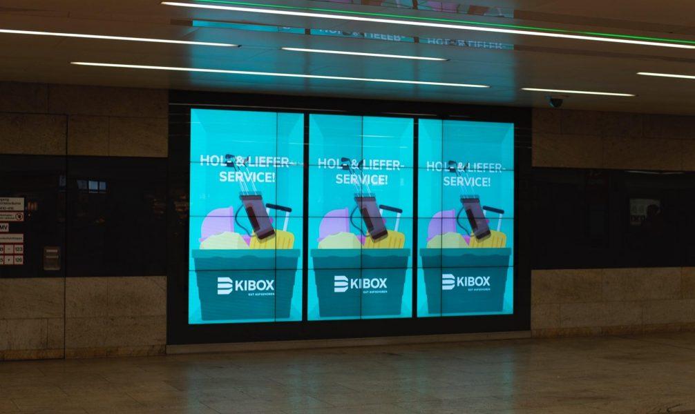 Außenwerbung für den Kunden KIBOX bei der eine Bahn beklebt wurde in der Farbe Grün mit vielen Gegenständen drauf die man einlagern kann