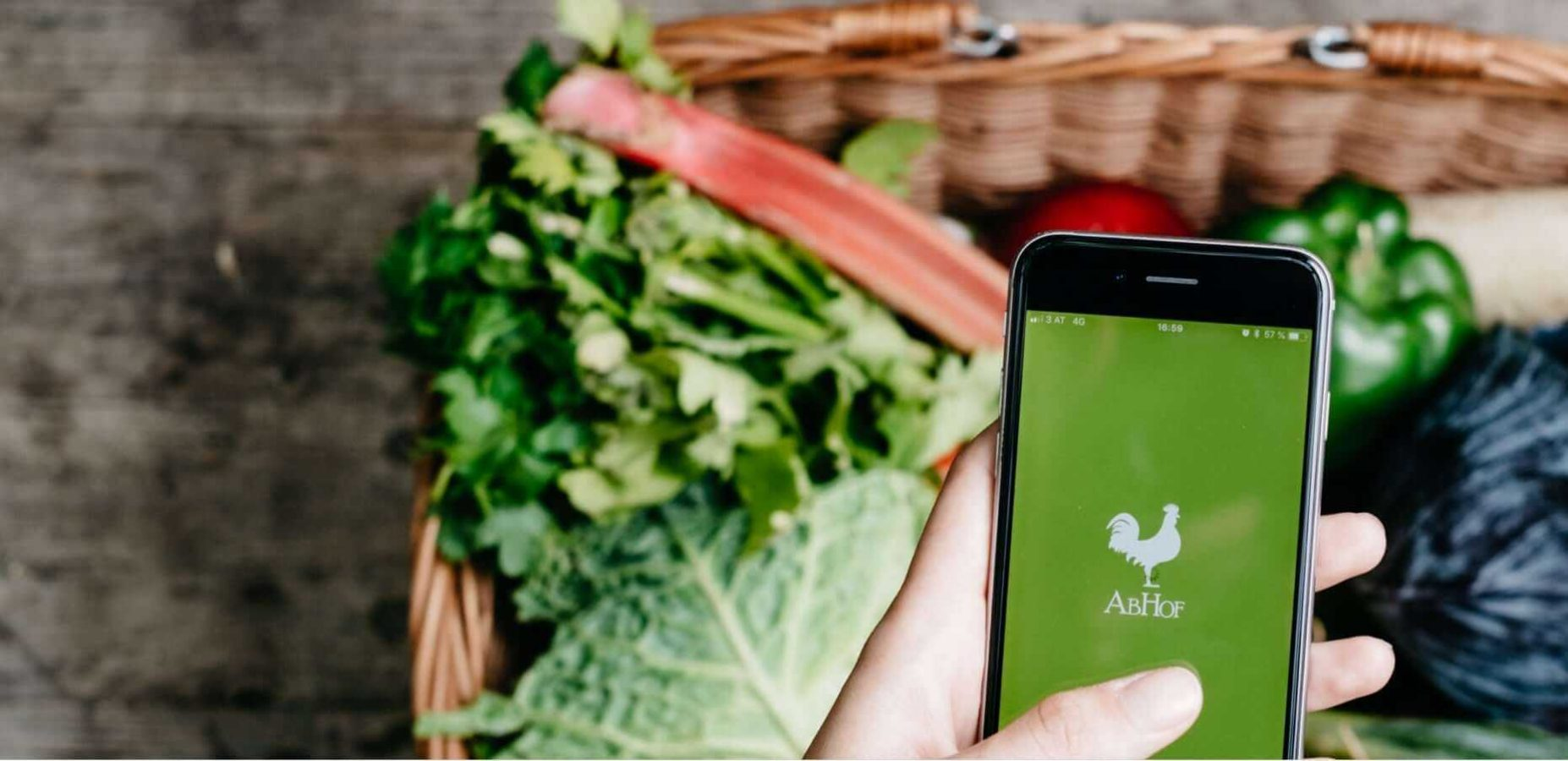 Die Abhof App im Fokus mit Gemüse im Hintergrund